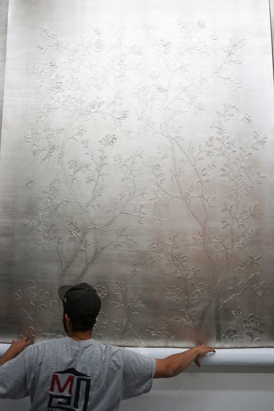 Rolling up a sculpted silver leafed panel